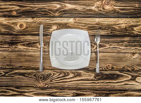 cutlery - fork knife and spoon on a wooden table
