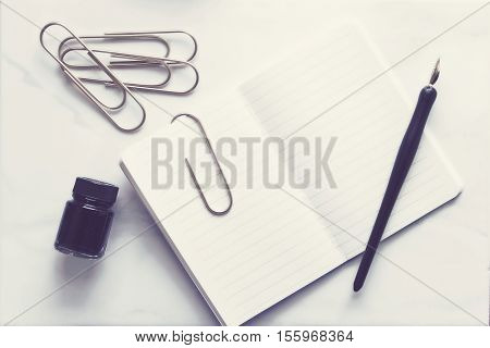 Over head flat lay view of a simple open notebook, pen and ink and paperclips.