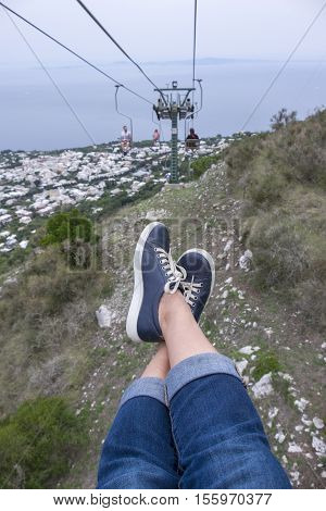 Feet and Legs Hanging from Chairlift Up to Mount Solaro in Anacapri Italy