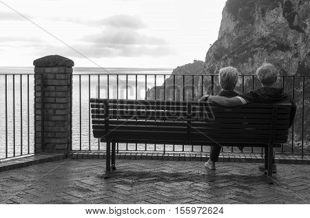 Black and white photograph of an elderly couple sitting on a park bench