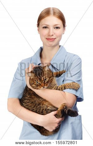 Young beautiful veterinarian woman in surgical coat hugging healthy adult scared tabby cat in hands and smiling isolated on white background