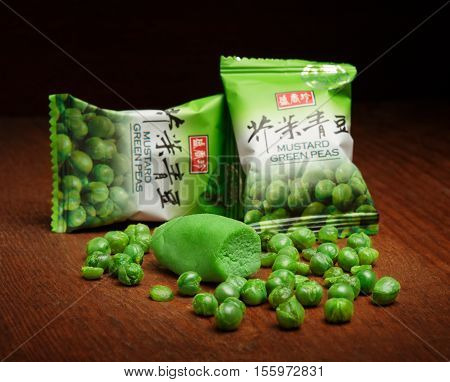 KYIV UKRAINE - JANUARY 19 2016. Editorial photo of Mustard Green Peas snack with wasabi by Triko Sheng Xiang Zhen Taiwanese company at wooden background. Shallow dof.