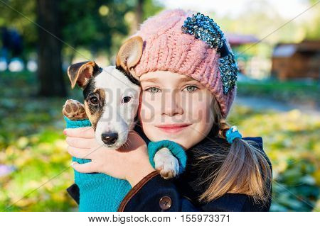 Little girl and her puppy portrait on park closeup