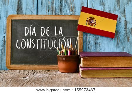 a chalkboard with the text dia de la constitucion, constitution day written in spanish, a pot with pencils, the flag of Spain and some old books, on a rustic wooden surface