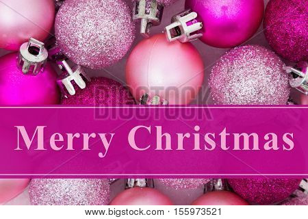 Merry Christmas greeting Some pale and bright pink sparkle and matte Christmas ball ornaments with text Merry Christmas