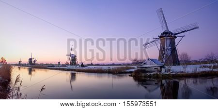 Sunrise over the windmills at the famous dutch UNESCO site Kinderdijk with some snow and reflection in the water of the canal in winter in the Netherlands.