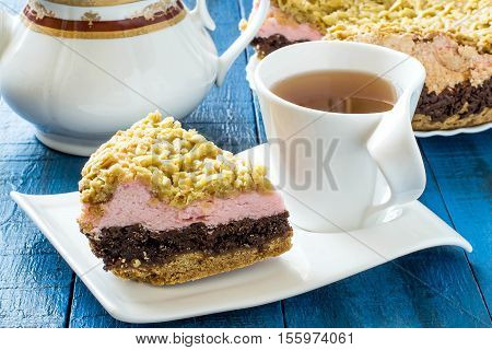 Homemade festive multilayer cake with jam chocolate marshmallows streusel and a cup of tea on a blue wooden background. Selective focus
