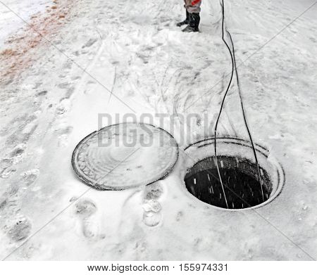 Mounting of fiber optical system in winter in snowfall and ice. Two cables hang down in open manhole of city sewerage. On background blur leg of worker in uniform.