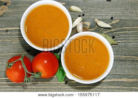 Overhead view of two bowls of tomato basil soup on wooden background with garlic peppers basil leaves bay leaves and tomatoes