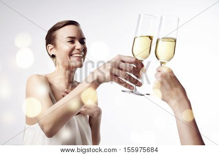 Woman celebrating and says cheers at the party with a glass of champagne. Clang glasses together