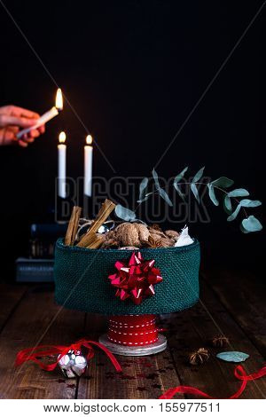 A Christmas Table Centrepiece, decorated with Ribbons and  filled with Walnuts, Cinnamon Sticks and Star Anise, against a Candlelit Background
