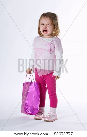 sad girl with shopping bag on white background