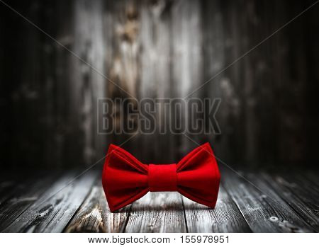 Christmas Decoration In Vintage Toning On Dark Black Wooden Background With Knitting Red Bowtie. Xma