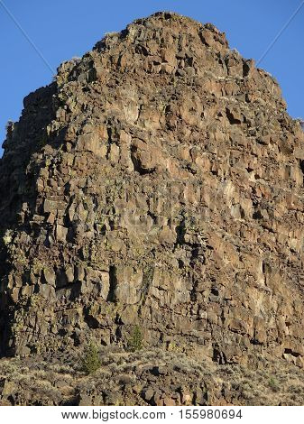 Jagged geology bursts from a hilltop on a sunny day in Crook County in Central Oregon.