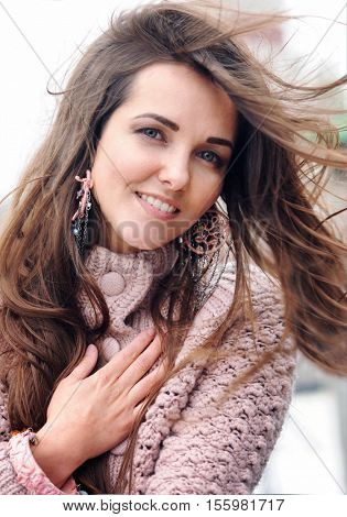 Beautiful smiling brunette woman portrait, chic long hair fluttering in the wind, looking at camera