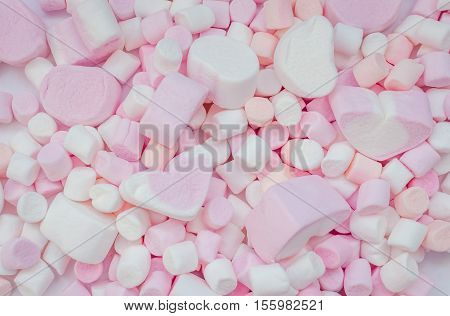 Colorful marshmallows background close-up texture. A pile of different mini white pink and orange in form of heart puffy marshmallows. Marshmallow concept. Wallpaper for desktop. Top view.
