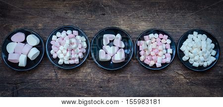 Colorful mini marshmallows in a black plates on a wooden background. Different mini white pink and orange puffy marshmallows. Marshmallow concept.