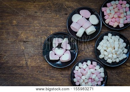 Colorful mini marshmallows in a black plate on a wooden background with place for text. Different mini white pink and orange puffy marshmallows. Marshmallow concept. Top view. Copy space.