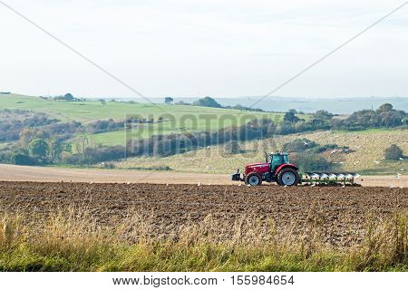 Red tractor ploughing a field on the South Downs near Devil's Dyke