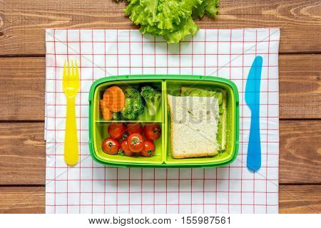 green lunch box for kid on dark wooden background top view