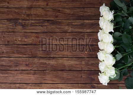 Thirteen white roses on a wooden background in line with the right hand with a place for an inscription