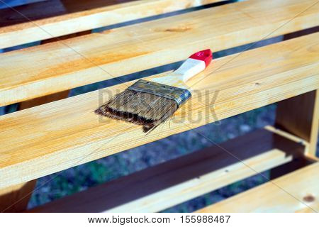 Brush lying on a painted wooden shelving surface. Horizontal photo outdoors closeup
