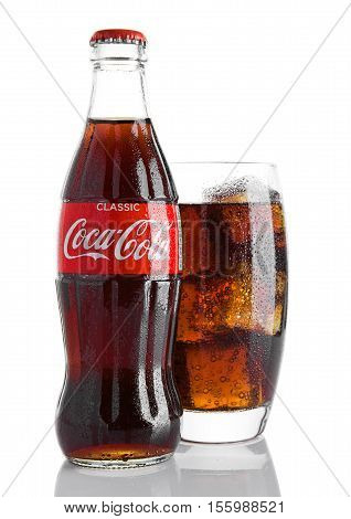 LONDON UK - NOVEMBER 07 2016: Classic bottle Of Coca-Cola with glass and ice cubes on white background