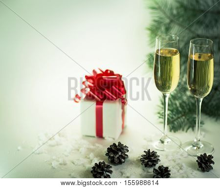 two glasses with champagne and Christmas gift on holiday background. the photo has a empty space for your text