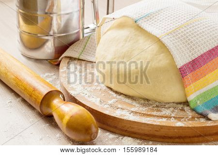 Special yeast dough for making braided cakes pies and rolls on a round board with a towel. During preparation the heat is eliminated getting ready in the refrigerator
