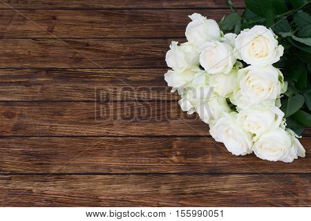 thirteen white roses on a wooden background with a place for an inscription