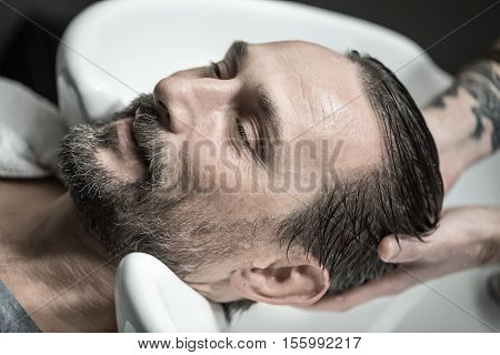 Cheerful man with a beard and in the barbershop. His head lies in the white sink and a barber with tattoo washes it. Closeup. Horizontal.