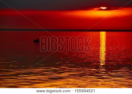 The good red sunset over darken sea.