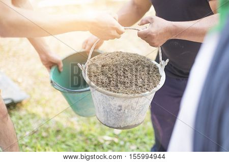 Older Labor Or Workers Carrying Construction Sand For Mix With Cement And Building Houses. Two Men A