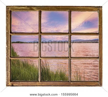 sunset over a lake with Rocky Mountains in background as seen from a sash window of an old cabin