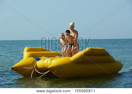 two children with mom on the dinghy sailing on the sea in summer.