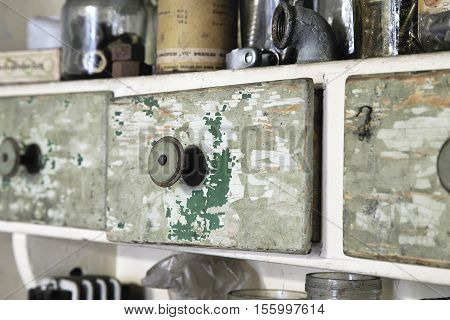 Vintage old wooden drawer in cupboard in workshop. Closeup closed. Green lacquer