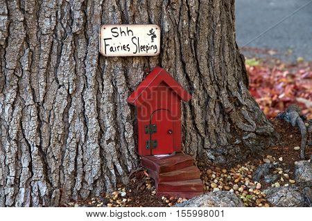 Alameda CA - November 10 2016: An urban art movement of tiny fairy doors hitting the curbs trees and public spaces on the Island of Alameda California spreading a little whimsy.