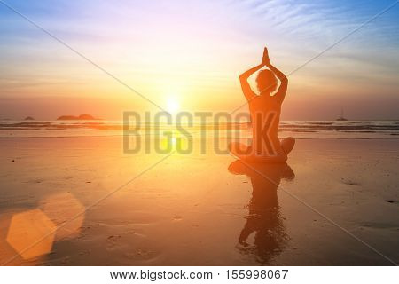 Female silhouette in yoga Lotus pose on the beach during an awesome sunset.