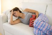 young beautiful hispanic woman in painful expression holding hot water bottle against belly suffering menstrual period pain lying sad on home couch having tummy cramp in female health concept poster
