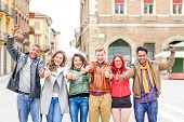 Multicultural group of friends thumbs up exulting successful day at old town square - Multiracial row of students positive attitude celebrating victory - Different skin color people united together poster