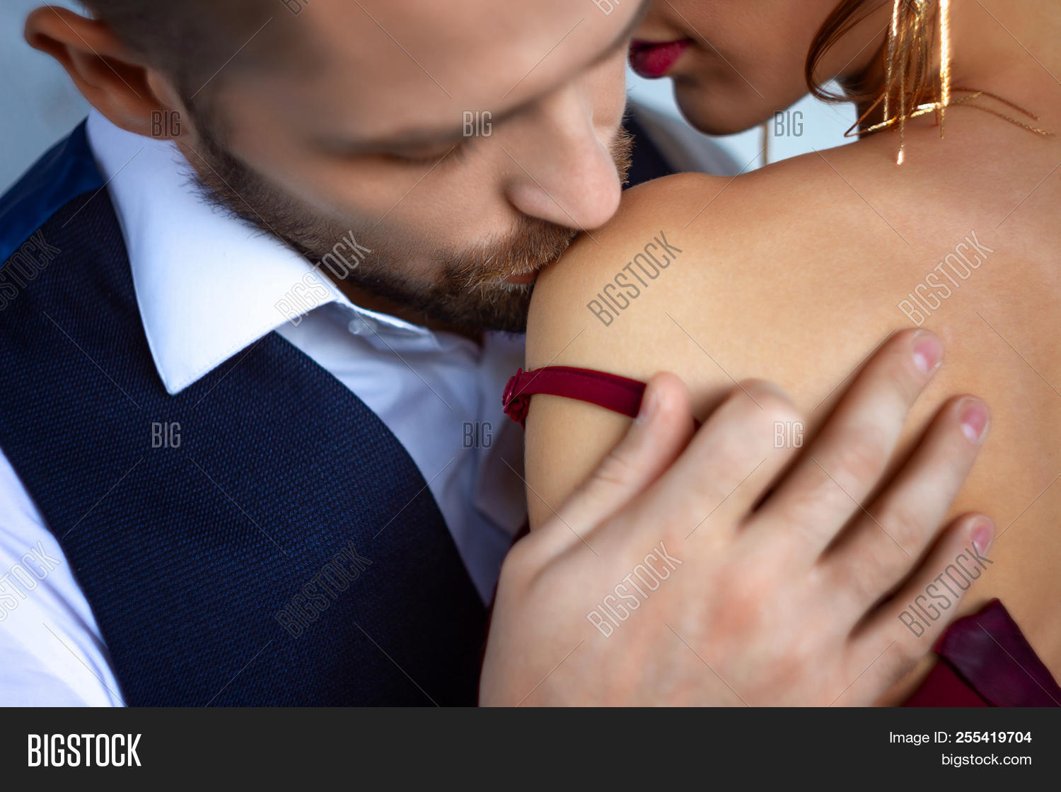 f3400a381 Elegant couple in love. Rich tidy neat man male kissing in shoulder of luxury  woman female in red evening dress with expensive gold earrings.