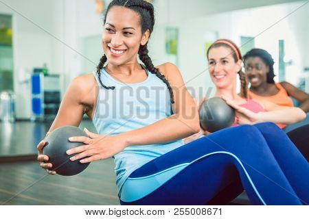 Beautiful young woman exercising Russian twist with med ball from sitting position for strong abs during group workout class for women at the gym