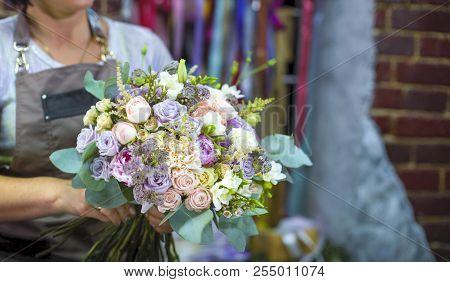 Professional Florist Arranging Wedding Bouquet In Floral Design Studio. Caucasian Female Master In A