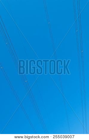 High voltage power line cables on blue sky poster