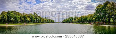 Tourist Walking Along The Reflecting Pool In Front Of The Washington Monument.