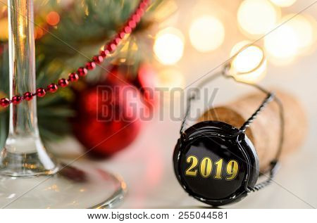 sparkling wine or champagne cork on table with christmas or new year 2019 blurred background and decorated fir-tree