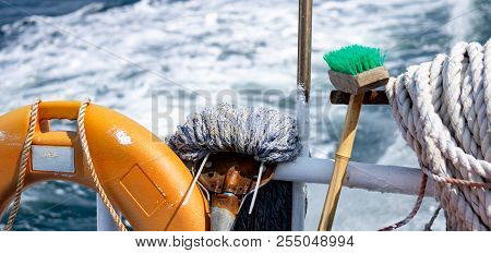 Cleanliness tool including mob and brush with handle, Safety buoy and old white rope at the stern of island ferry near coastalline in Geoje island, South Korea poster
