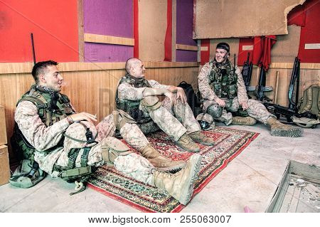 Soldiers Communicating And Resting After Mission On Outpost