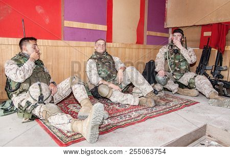 Soldiers Communicating And Resting After Mission At The Outpost