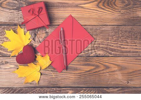 Autumn Background With Maple Leaves, Red Envelope, Pen, Gift Box, Knitted Heart On Wooden Boards. Co